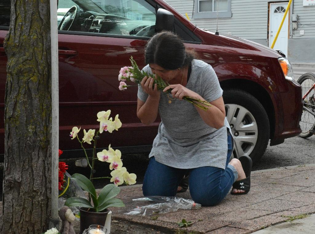 A woman leaves flowers for the victims at the scene of the shooting in Toronto, Ontario, Canada