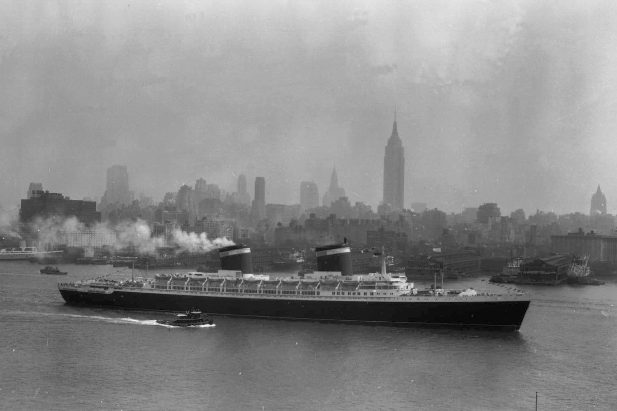 FILE - In this July 3, 1952 file photo, the SS United States glides down the Hudson River as it begins its first voyage to Europe from New York in view of the Midtown Manhattan skyline including the Empire State building on the center right. Money and time are running out for the historic ocean liner, which carried princes and presidents across the Atlantic in the 1950s and 1960s but has spent decades patiently awaiting a savior at its berth on the Philadelphia waterfront. The nonprofit conservancy working to secure a home and purpose for the 990-foot-long ship said it could be sold for scrap in the spring of 2013 unless they can raise $500,000 immediately. (AP photo/Jack Harris, File)