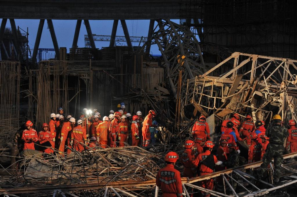 Workers search through the remains of a collapsed platform in a cooling tower at a power station at Fengcheng in China's Jiangxi province on November 24, 2016 (AFP Photo/)