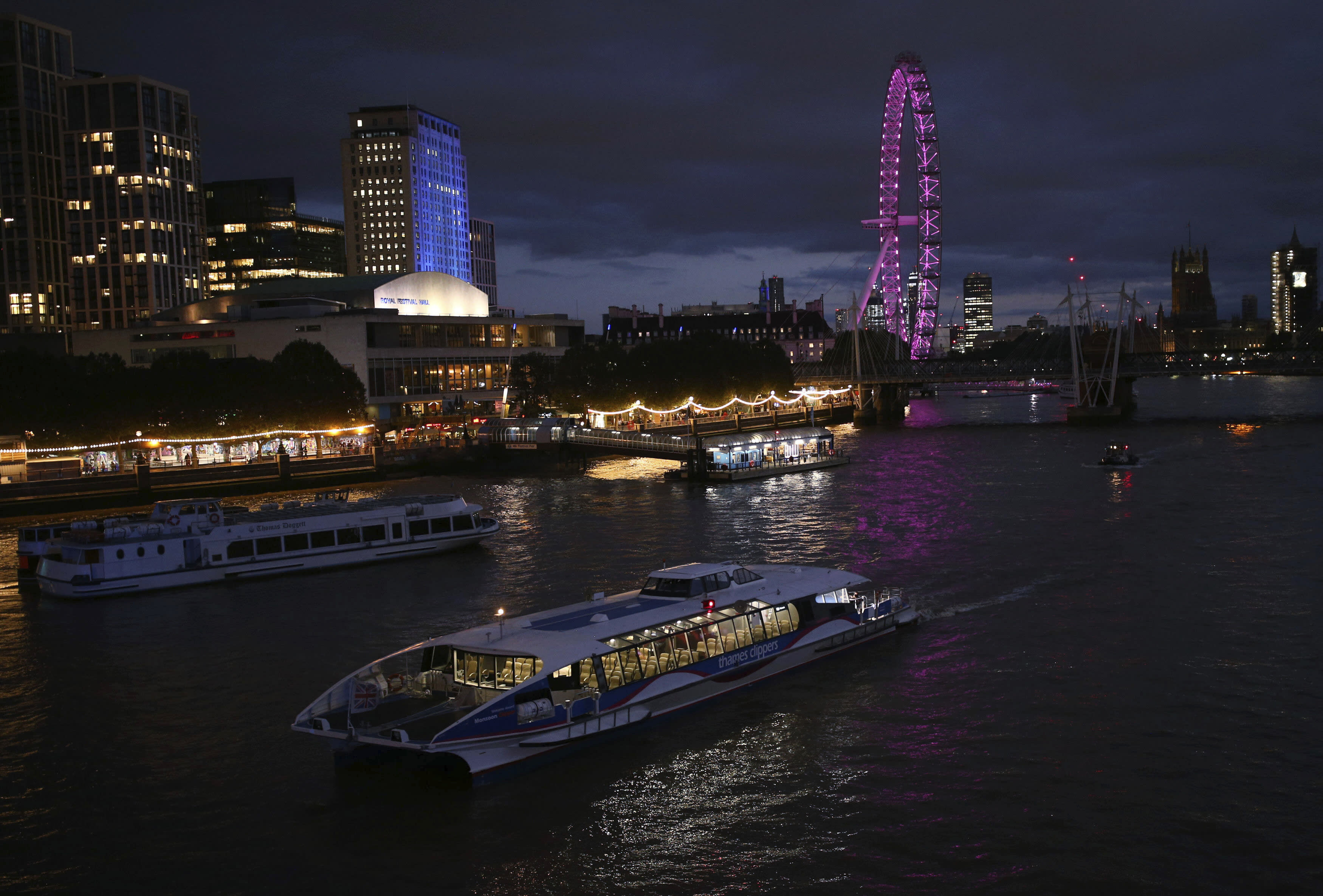 An almost empty Thames Clipper boat sails past the South Bank during the coronavirus pandemic on the River Thames, in central London, Tuesday, Sept. 8, 2020. (Yui Mok/PA via AP)