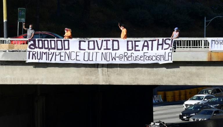 "Activists unfurl a banner reading ""200,000 Covid Deaths! Trump/Pence Out Now"" over a freeway in Los Angeles"