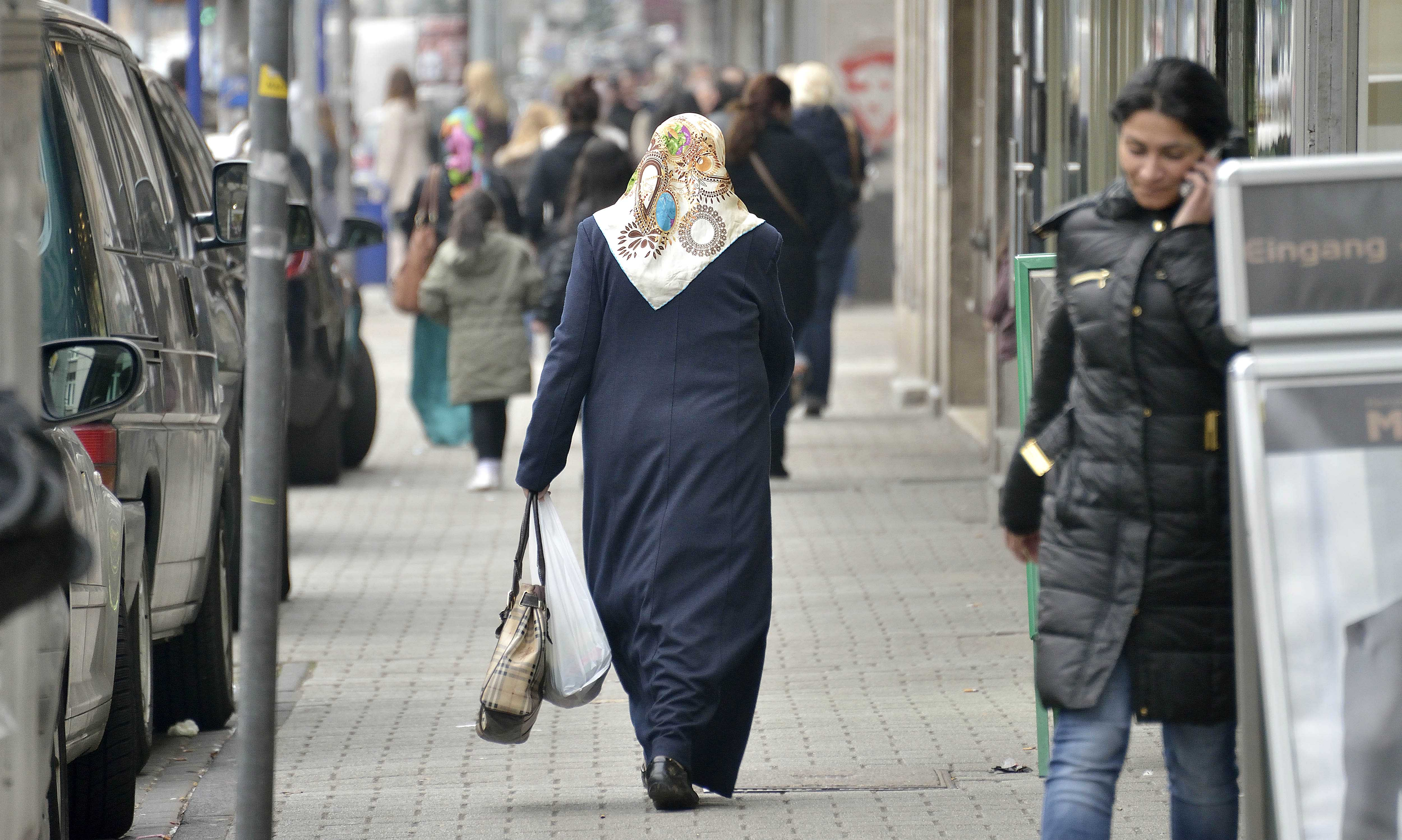 "In this picture taken March 7, 2013, Turkish immigrants walk the shopping streets in Dusiburg-Marxloh, western Germany.Germany's experience with ""guest workers"" offers lessons for the United States as it debates immigration reform, including whether to provide a path to citizenship for unskilled foreign laborers. (AP Photo/Martin Meissner)"