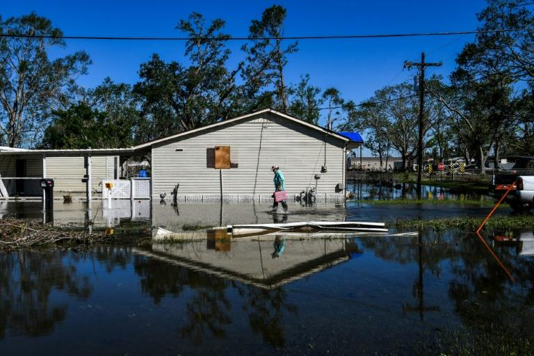 Daniel Schexnayder walks through his flooded yard in the small town of Iowa, Louisiana on October 10, 2020