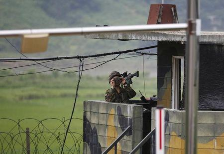 A South Korean soldier keeps watch at a guardpost near the demilitarized zone which separates the two Koreas, in Paju