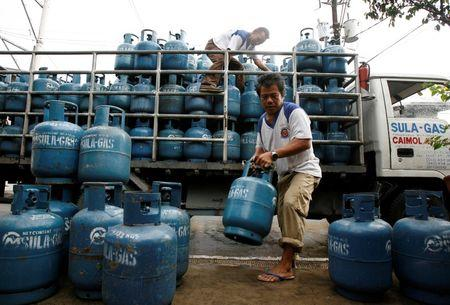 Workers deliver LPG tanks to a retailer in Manila