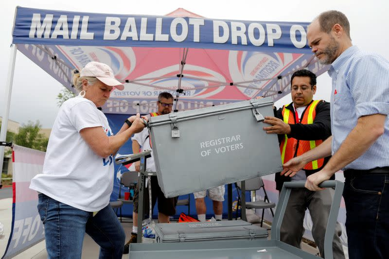 FILE PHOTO: Election workers take away a ballot box full of votes at a drive-through mail-in ballot return drop set-up outside the Registrar of Voters office in San Diego