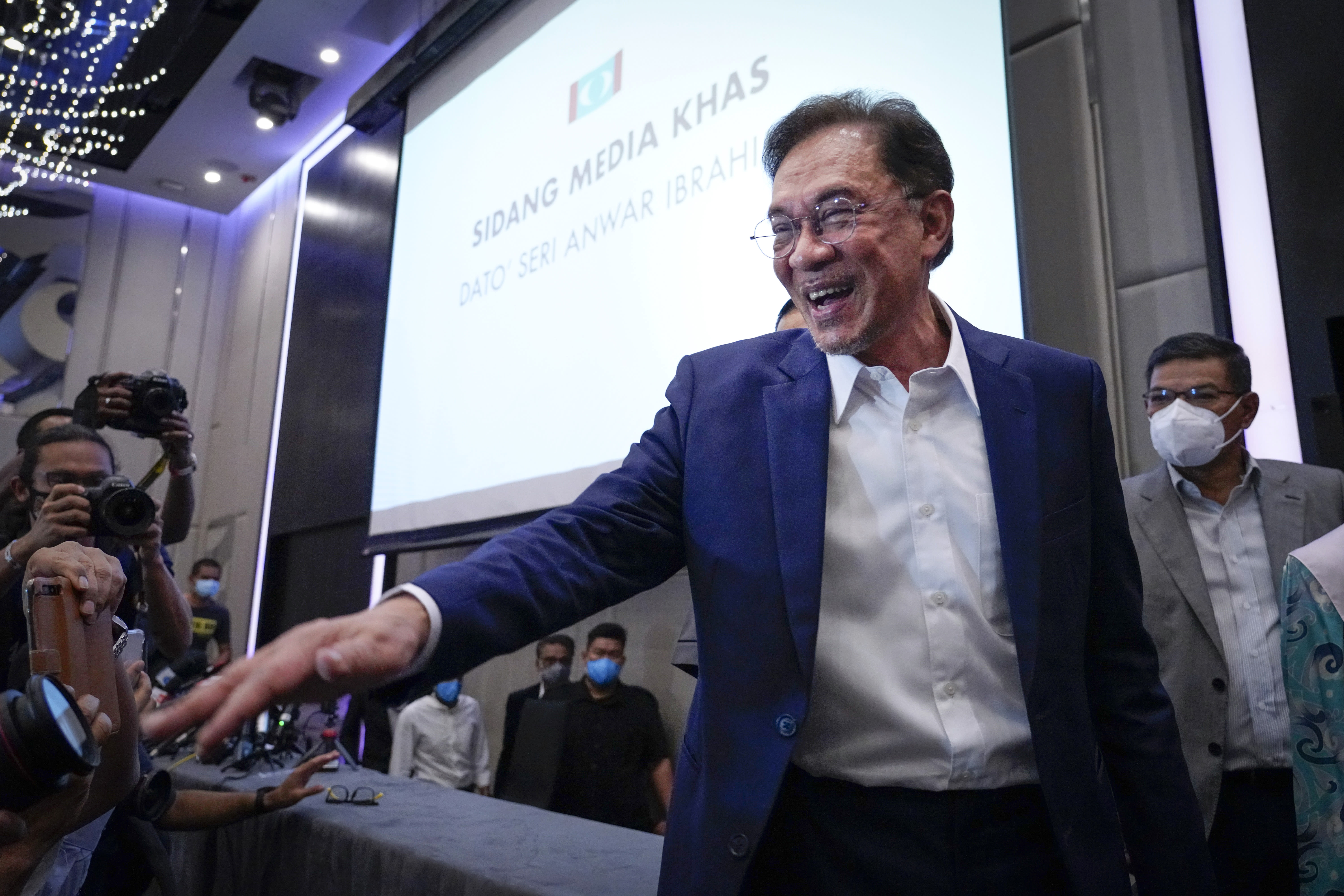 """Malaysia's opposition leader Anwar Ibrahim gestures as he leaves after a press conference in Kuala Lumpur, Wednesday, Sept. 23, 2020. Anwar said he has secured a majority in parliament to form a new government that is """"strong, stable and formidable."""" (AP Photo/Vincent Thian)"""