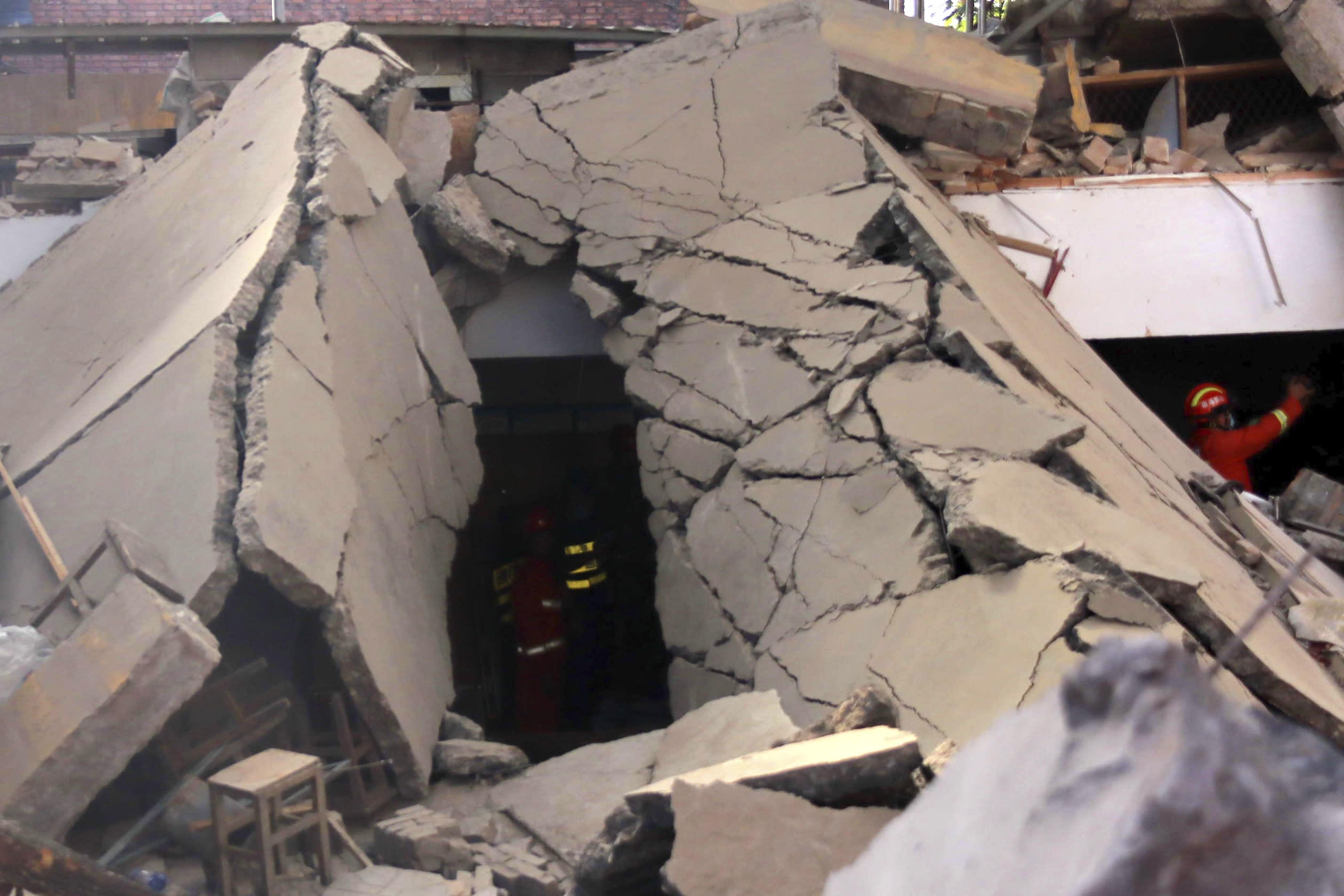 Rescuers search for victims in the aftermath of the collapse of a two-story restaurant in Xiangfen county in northern China's Shanxi province on Saturday, Aug. 29, 2020. More than a dozen were killed after the restaurant collapse during a gathering. (Chinatopix Via AP)