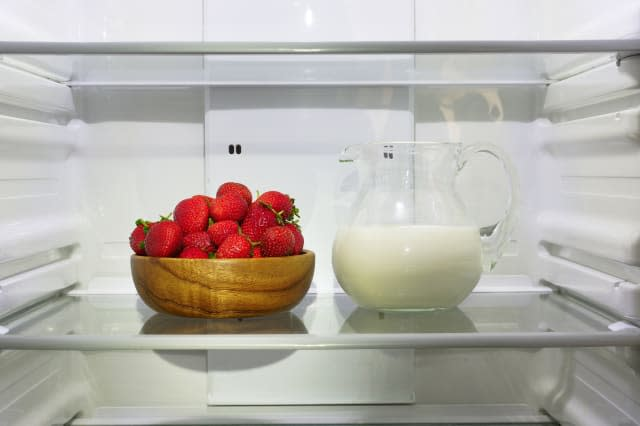 Strawberries and a pitcher of milk in the refrigerator.