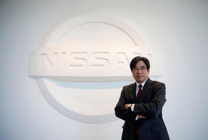 FILE PHOTO: President Sakamoto poses with the carmaker's logo in the showroom at the carmaker's headquarters in Yokohama