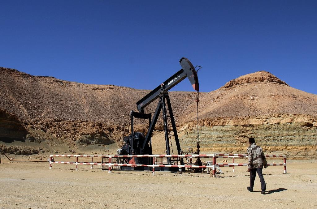 A Libyan security member walks past an oil drill on the al-Ghani oil field near the city of Waddan on March 23, 2013