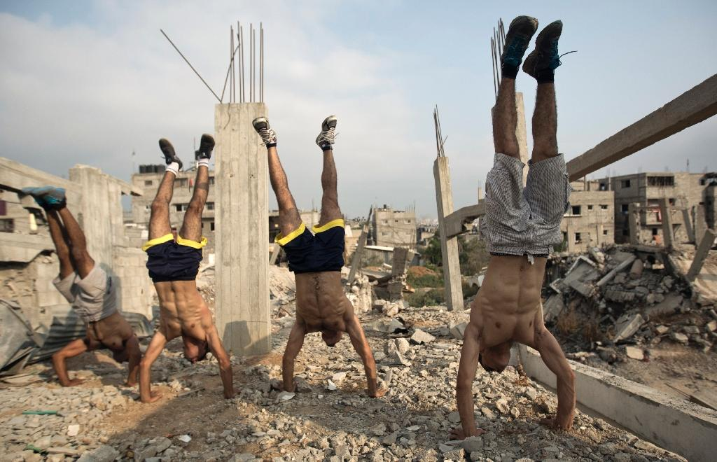 Palestinian group, Bar Palestine, perform handstands as part of street exercises, amid the destruction in Gaza City (AFP Photo/Mohammed Abed)