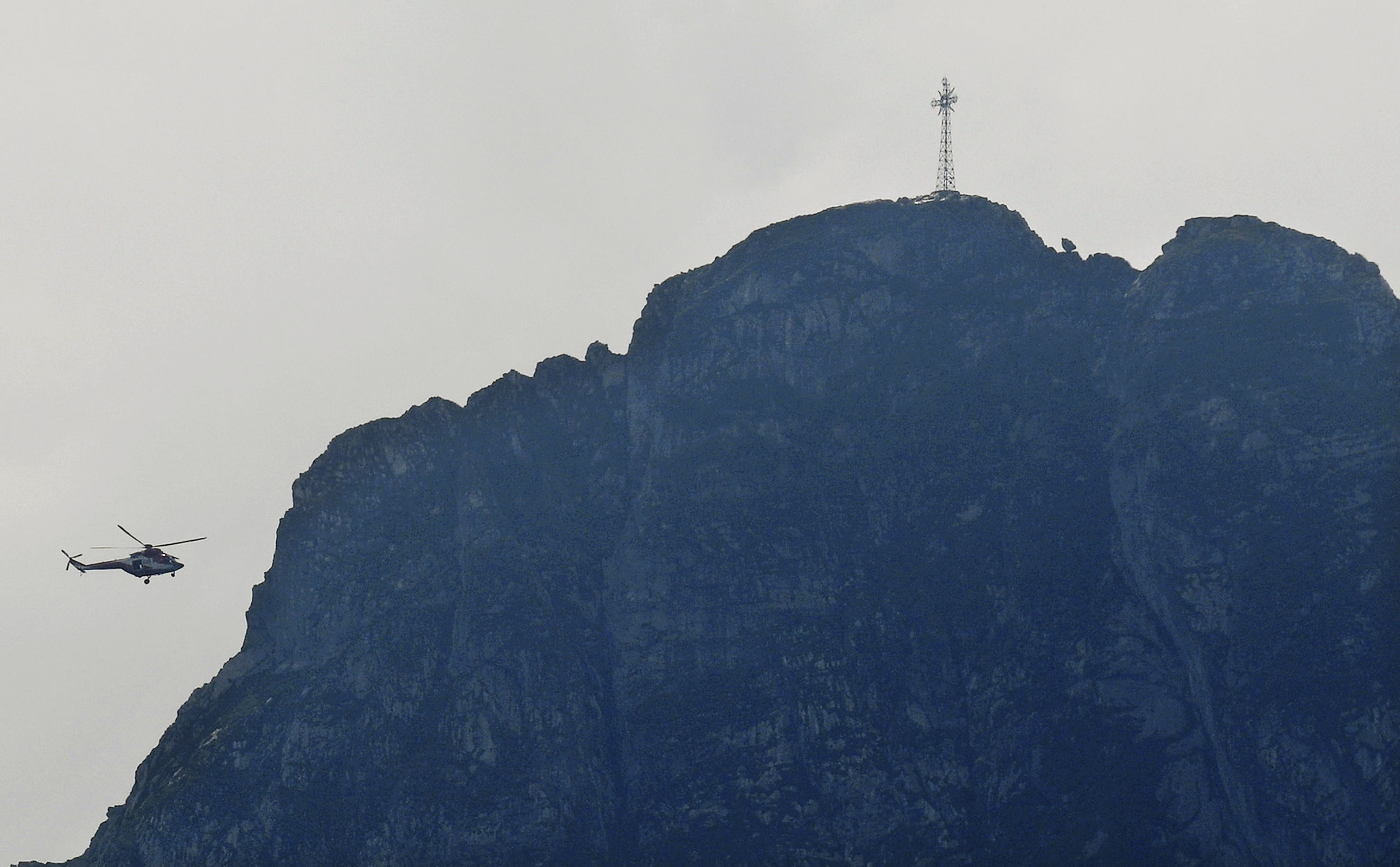 Rescuers in a helicopter checking the slopes of the Giewont peak for missing persons and anyone who might need help in the Tatra Mountains in Poland, Friday, Aug. 23, 2019. Three people are still missing in southern Poland after a deadly thunderstorm with multiple lightning strikes hit the Tatra Mountains, killing five people and injuring over 150. (AP Photo/Bartlomiej Jurecki)