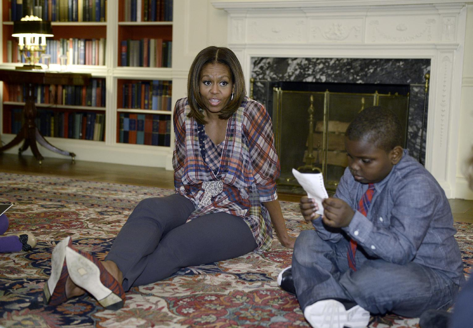 """First lady Michelle Obama sits on the floor with """"kid reporter"""" Justin Creppy, 6, from Upper Marlboro, Md., Monday, April 21, 2014, in the Library of the White House in Washington. (AP Photo/Susan Walsh)"""