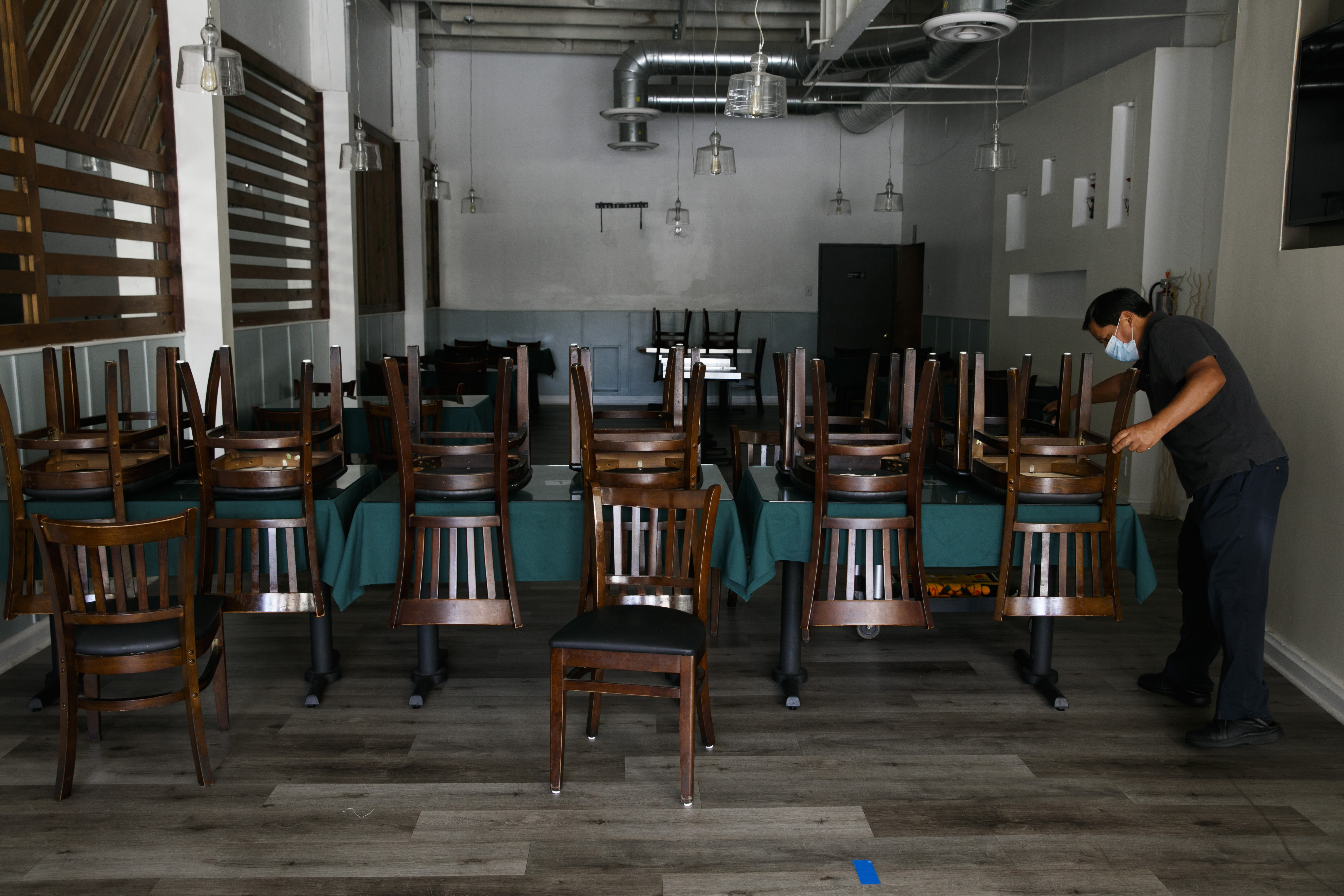 Fabian Nahui, the owner of a Peruvian restaurant, arranges chairs Monday, July 6, 2020, in Los Angeles. The coronavirus is blamed for over a half-million deaths worldwide, including more than 130,000 in the U.S., according to the tally kept by Johns Hopkins University. (AP Photo/Jae C. Hong)