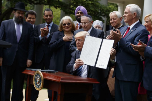 President Trump holds the executive order aimed at easing an IRS rule limiting political activity for churches, on May 4, 2017, in the White House Rose Garden.
