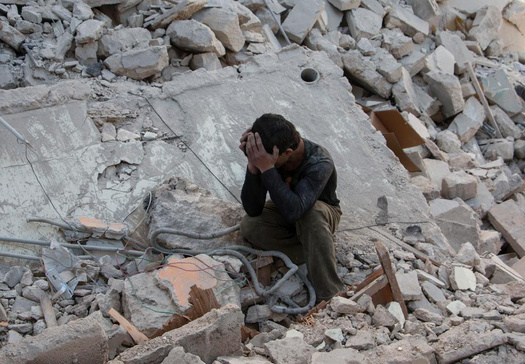 A Syrian boy in the rubble after a reported air strike by government forces on the rebel held area of Aleppo, on April 13, 2015 (AFP Photo/Karam Al-Masri)