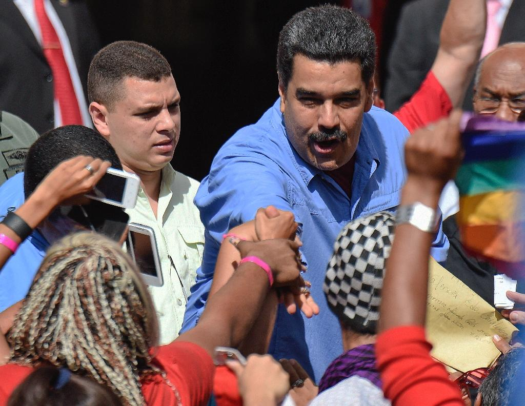Venezuelan President Nicolas Maduro shakes hands with supporters during a rally with women in Caracas on May 24, 2016 (AFP Photo/Juan Barreto)