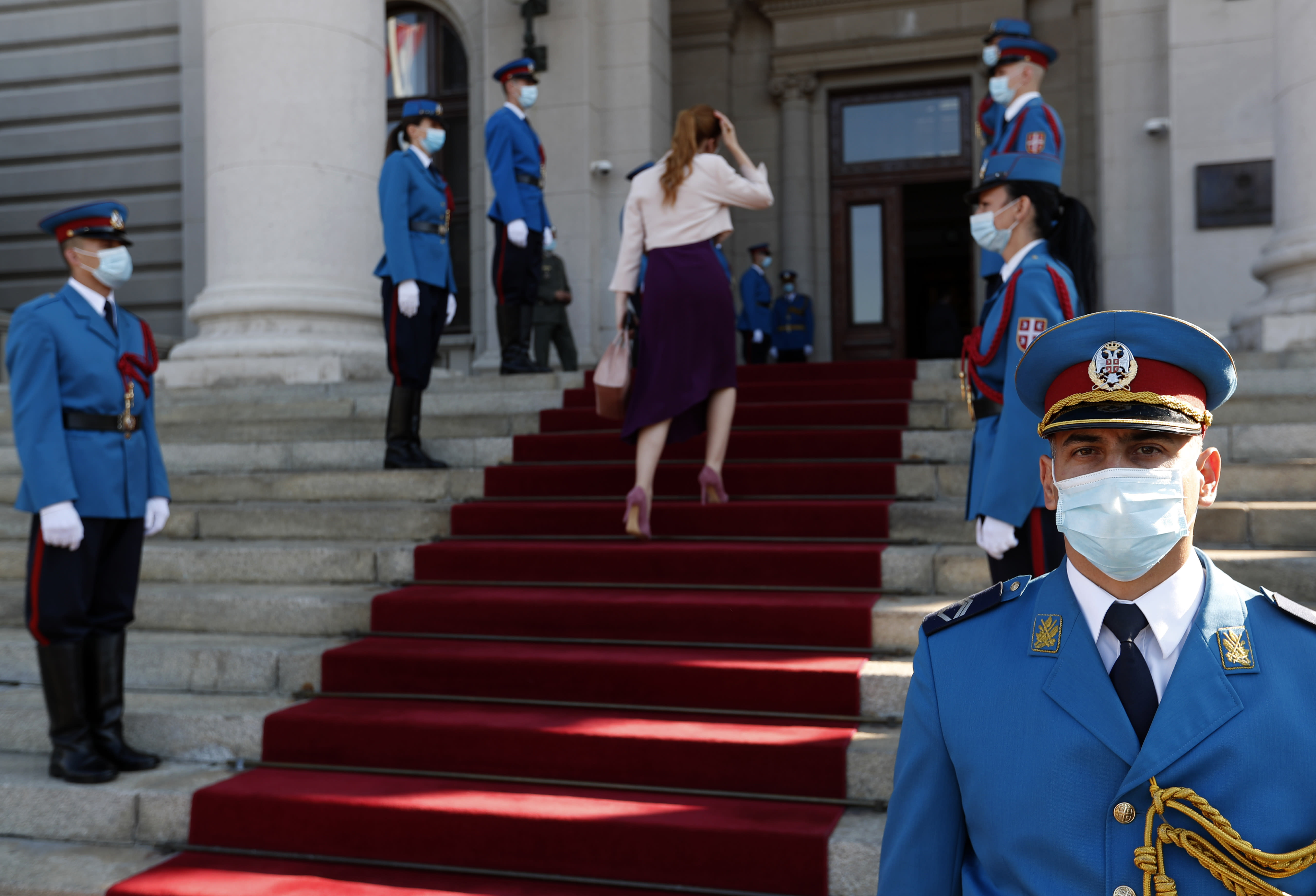 Serbia's army guard of honor wearing face masks to prevent the spread of coronavirus, stand in front of the parliament building before the inaugural parliament session in Belgrade, Serbia, Monday, Aug. 3, 2020. The Serbian parliament reconvened Monday amid protests by opposition and far-right supporters who claim the parliamentary election that was overwhelmingly won by the ruling populists was rigged. (AP Photo/Darko Vojinovic)