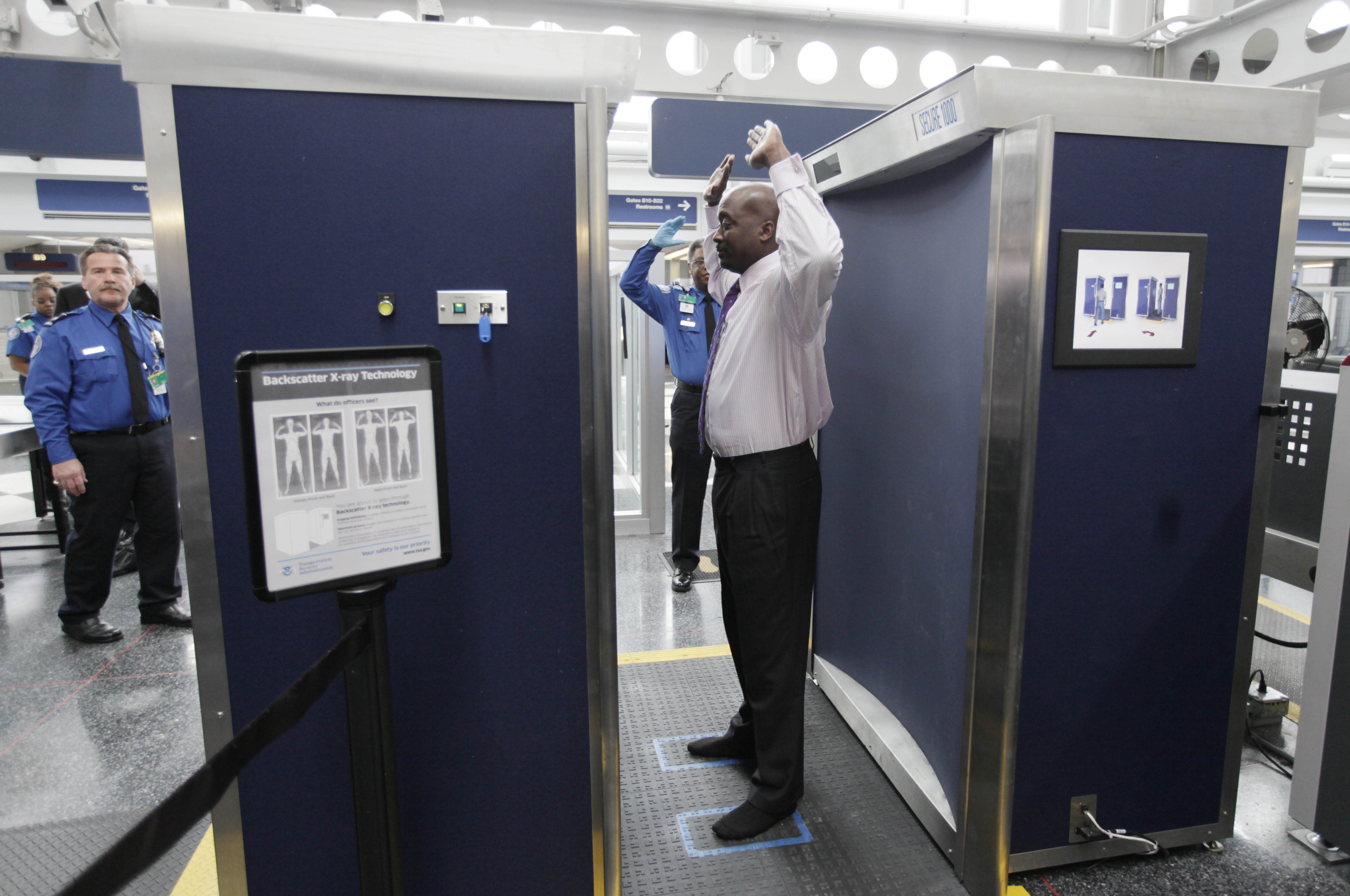 FILE - In this March 15, 2010 file photo, a volunteer passes through the first full body scanner installed at O'Hare International Airport in Chicago. The Transportation Security Administration has been replacing the huge X-ray machines with smaller, millimeter wave body scanners at seven major U.S. airports. The new technology produces a cartoon-like outline rather than naked images of passengers produced by using X-rays. (AP Photo/M. Spencer Green, File)