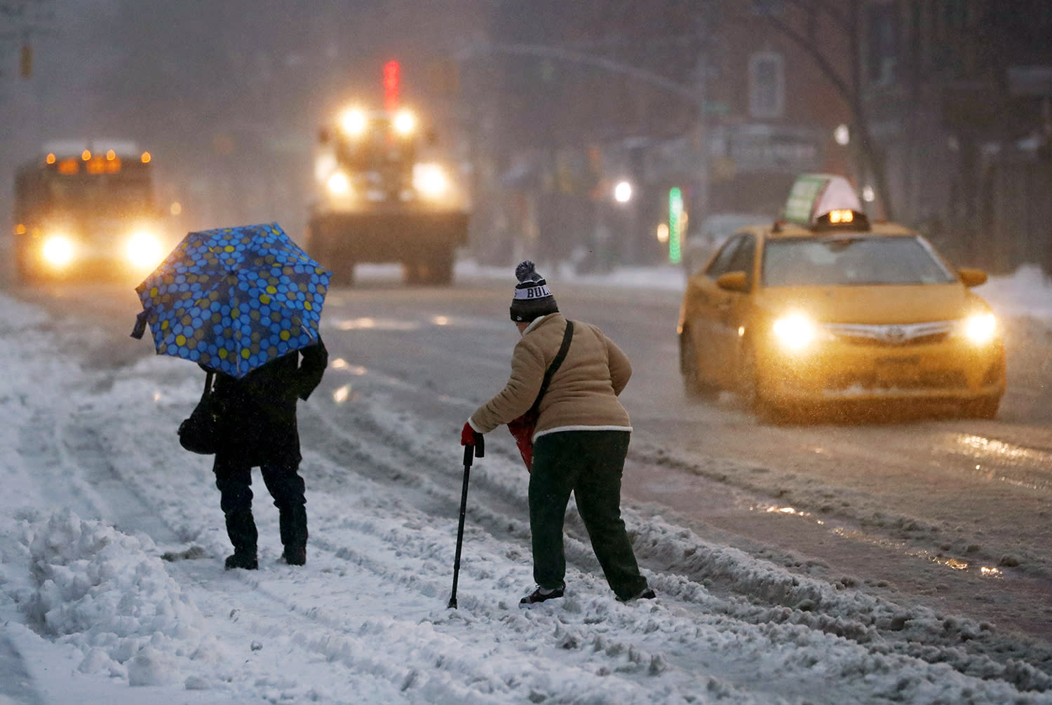 <p>Women try to cross a snow-covered street in New York, March 14, 2017. While New York and Boston had been issued a blizzard warning, that has been downgraded to a winter storm as the storm's track shifted resulting in a shift to rain for both cities and smaller forecast snowfall totals. (Jason Szenes/EPA) </p>