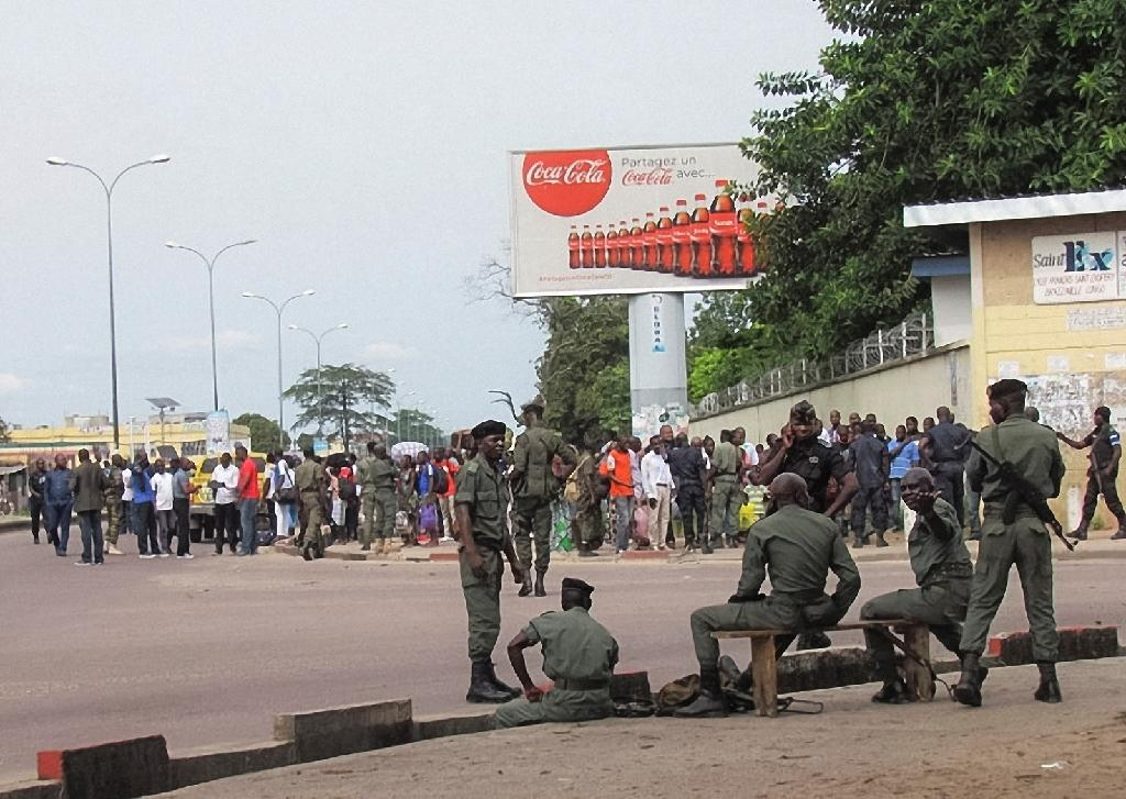 Security forces stand guard as residents of the southern districts of Brazzaville flee clashes between Congolese security forces and unknown assailants on April 4, 2016 (AFP Photo/STRINGER)