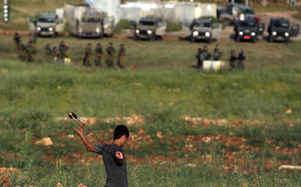 A Palestinian youth uses a sling shot to throw stones towards members of the Israeli security forces during clashes after a house belonging to a Palestinian family was demolished by Israeli bulldozers (AFP Photo/Abbas Momani)