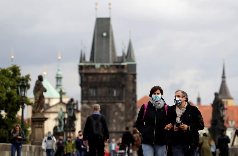 People wearing face masks walk in Prague