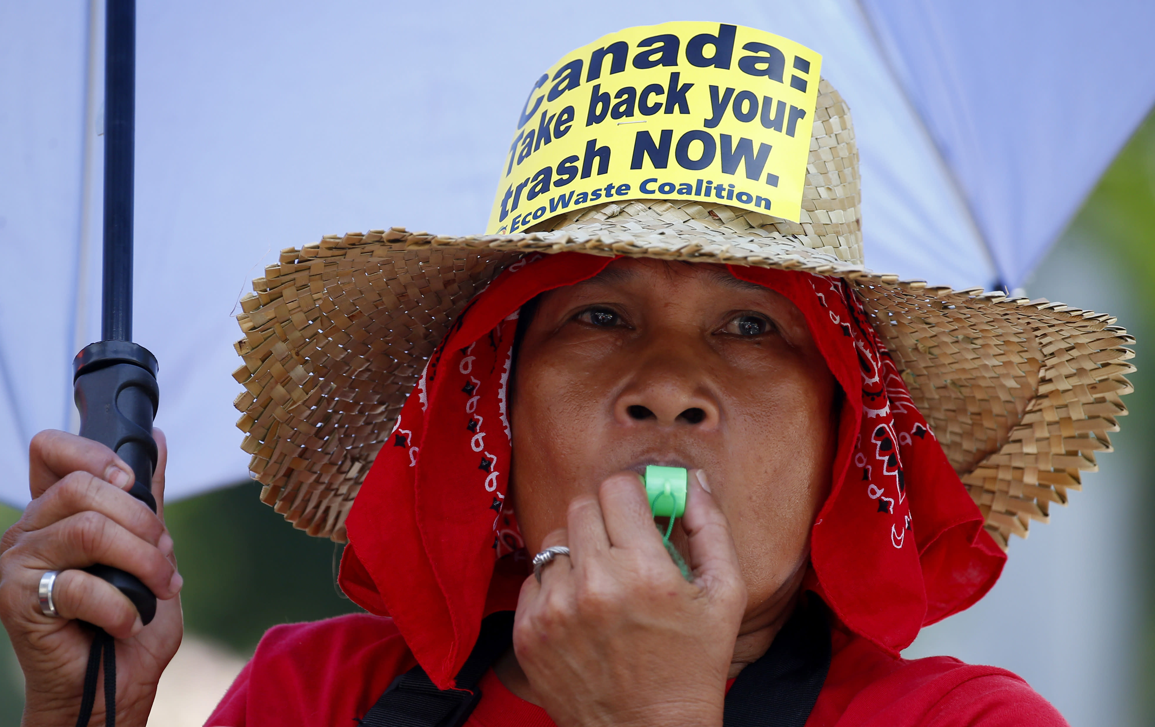 An environmentalist blows her whistle during a protest outside the Canadian Embassy to demand the Canadian government to speed up the removal of several containers of garbage that were shipped to the country Tuesday, May 21, 2019, in Manila, Philippines. The Philippines recalled its ambassador and consuls in Canada last week over Ottawa's failure to comply with a deadline to take back 69 containers of garbage that Filipino officials say were illegally shipped to the Philippines years ago. (AP Photo/Bullit Marquez)