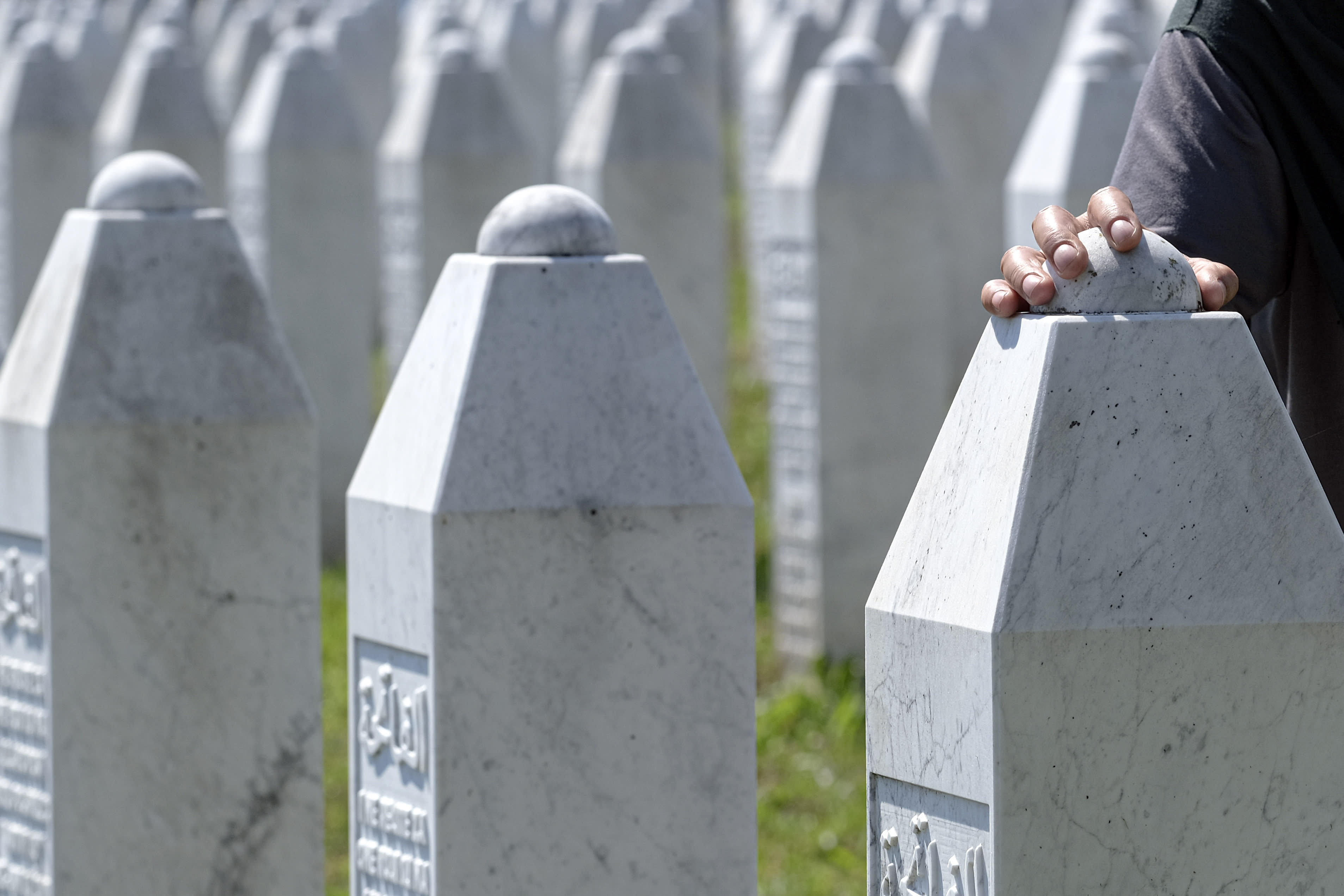 A woman touches a grave stone in Potocari, near Srebrenica, Bosnia, Saturday, July 11, 2020. Mourners converged on the eastern Bosnian town of Srebrenica for the 25th anniversary of the country's worst carnage during the 1992-95 war and the only crime in Europe since World War II that has been declared a genocide. (AP Photo/Kemal Softic)