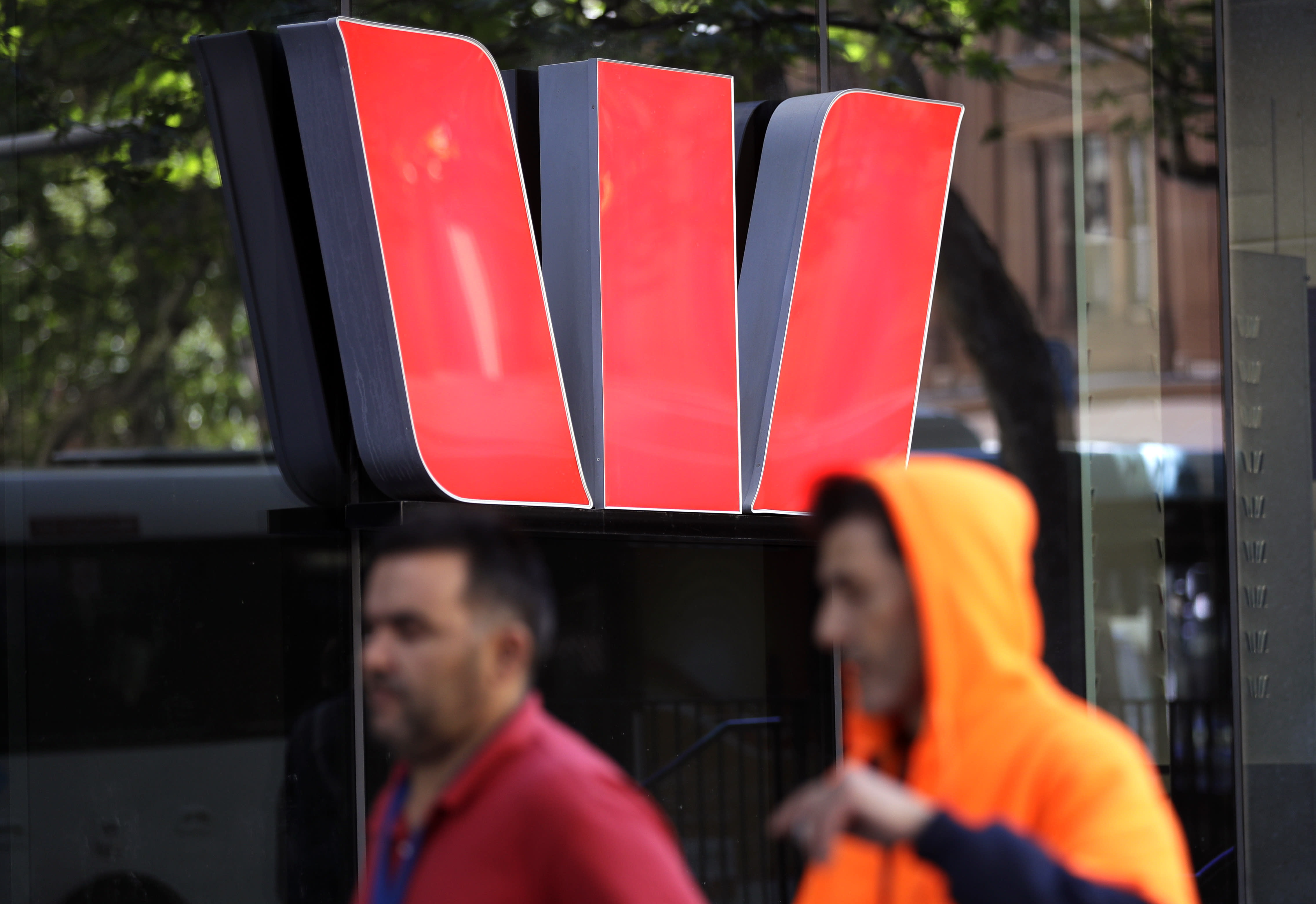 Two men walk past a Westpac bank branch in Sydney, Thursday, Sept. 24, 2020. Westpac, Australia's second-largest bank, agreed to pay a 1.3 billion Australian dollar ($919 million) fine for breaches of anti-money laundering and counterterrorism financing laws, the largest ever civil penalty in Australia, a financial crime regulator said. (AP Photo/Rick Rycroft)