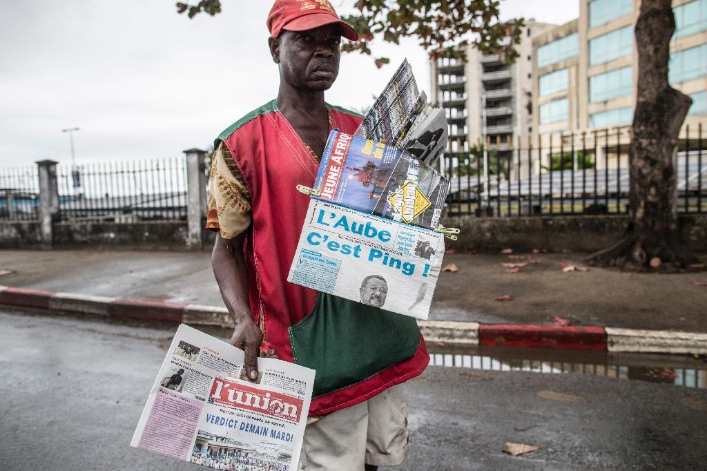A newspaper vendor looks for customers in Libreville on August 29, 2016 while displaying local papers reporting on the outcome of Gabons's presidential elections (AFP Photo/Marco Longari)