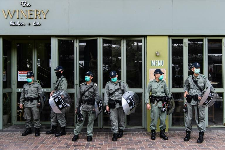Riot police stand guard near a group of pro-democracy protesters in Hong Kong who are stopped for breaking restrictions on social distancing during the coronavirus pandemic