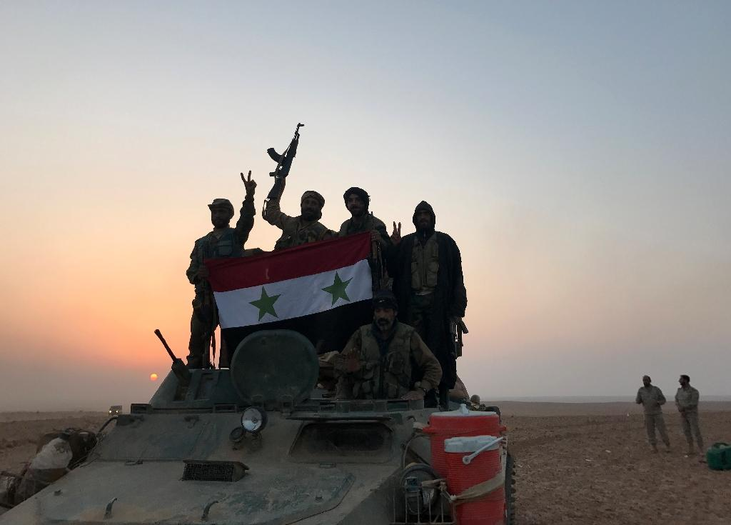Syrian forces gestures as they carry the national flag in the village of Suway'iah, near the Syrian border town of Albu Kamal, on November 9, 2017 (AFP Photo/STRINGER)