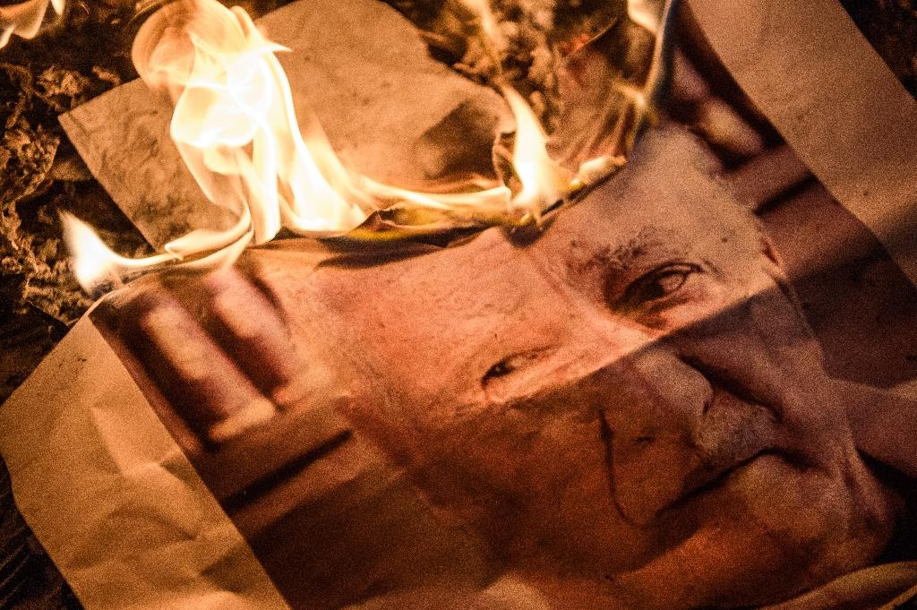 Pro-Erdogan supporters burn a poster picturing US-based preacher Fethullah Gulen during a rally at Taksim square in Istanbul (AFP Photo/Ozan Kose)