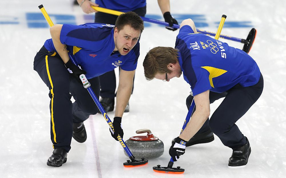 Sweden's Fredrik Linberg, left, and Sebastian Kraupp, right, sweep ahead of the stone during the men's curling match against Britain at the 2014 Winter Olympics, Sunday, Feb. 16, 2014, in Sochi, Russia