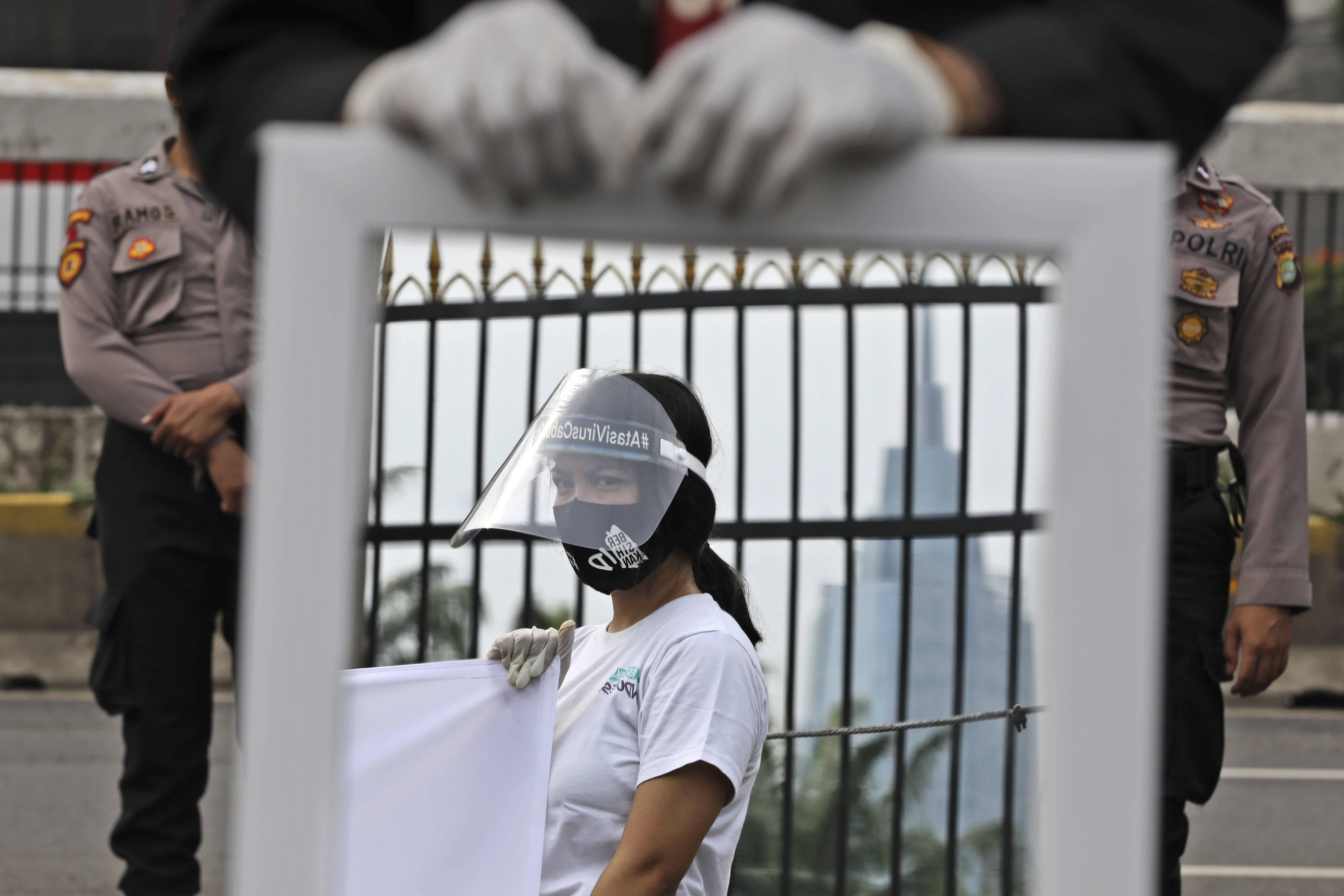 A mirror reflects the image of an activist wearing a mask and protective face shield as a precaution against the new coronavirus outbreak during a small protest outside the parliament in Jakarta, Indonesia, Tuesday, July 14, 2020. About a dozen activists staged the protest opposing the government's omnibus bill on job creation that was intended to boost economic growth and create jobs, saying that it undermined labor rights and environmental protection. (AP Photo/Dita Alangkara)