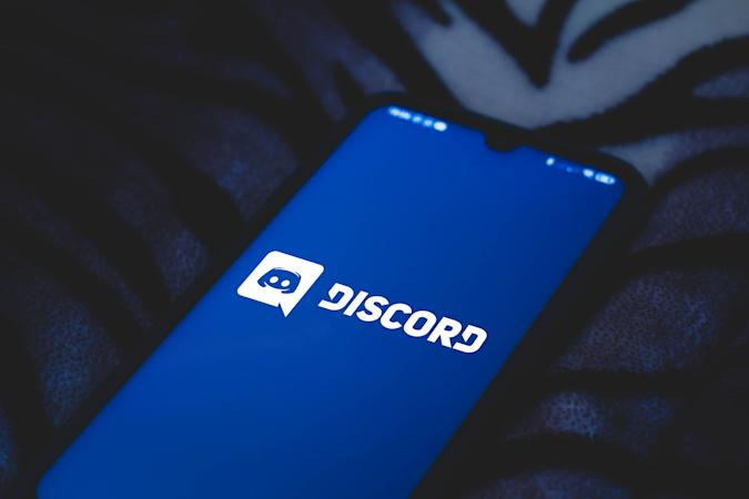 In this photo illustration a Discord logo seen displayed on...