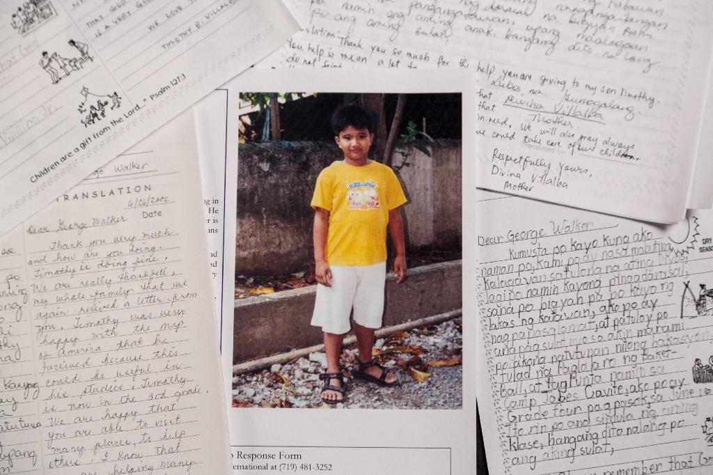 Timothy, then a seven-year-old Filipino boy, is shown in a photograph with a letter he sent to his pen pal, former US President George H.W. Bush, who sponsored him for 10 years using a pseudonym (AFP Photo/Handout)