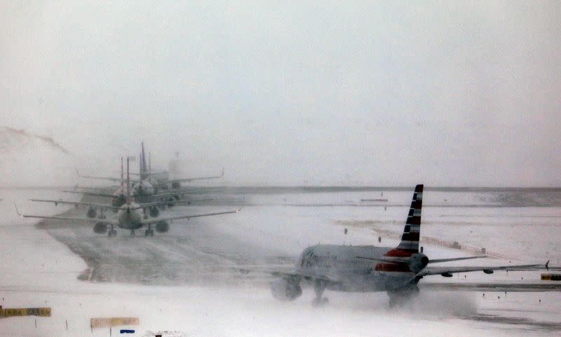 FILE PHOTO: A line of jets wait to takeoff after a snowstorm at Denver International Airport