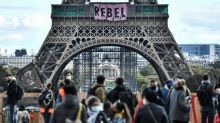 Mitglieder von Extinction Rebellion klettern am Eiffelturm hoch