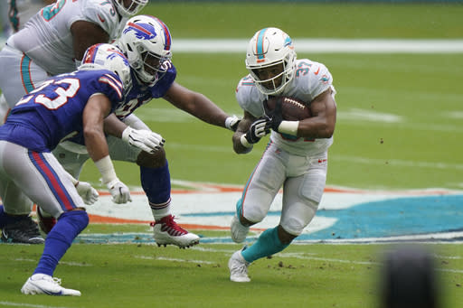 Miami Dolphins running back Myles Gaskin (37) runs the ball A Buffalo Bills strong safety Micah Hyde (23) attempts to stop him, during the first half of an NFL football game, Sunday, Sept. 20, 2020 in Miami Gardens, Fla. (AP Photo/Wilfredo Lee)