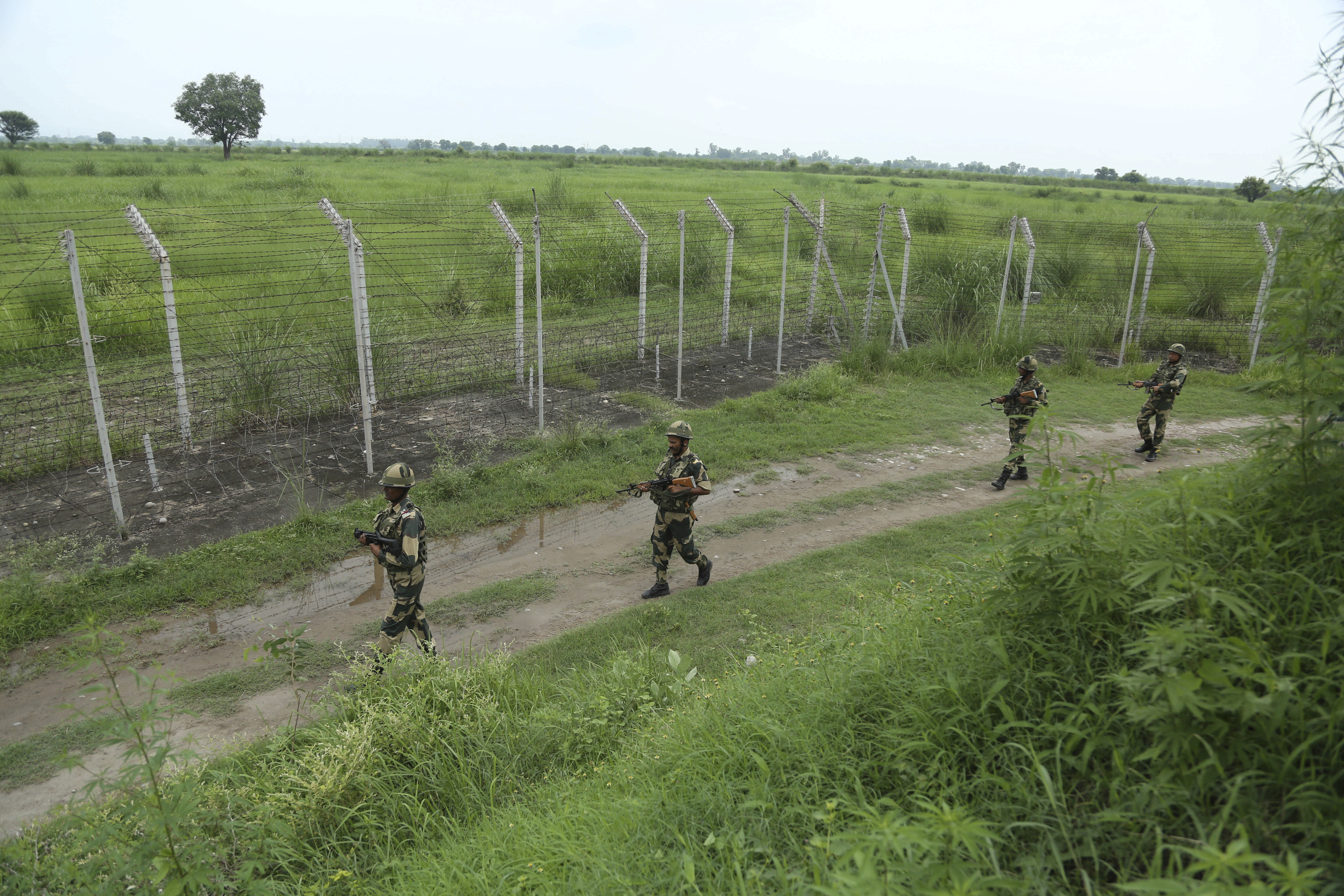India's Border Security Force (BSF) soldiers patrol near the India Pakistan border fencing at Garkhal in Akhnoor, about 35 kilometers (22 miles) west of Jammu, India, Tuesday, Aug.13, 2019. Pakistan has denounced India's actions to change the special status of the disputed Himalayan region of Kashmir and has downgraded its diplomatic ties with New Delhi. (AP Photo/Channi Anand)