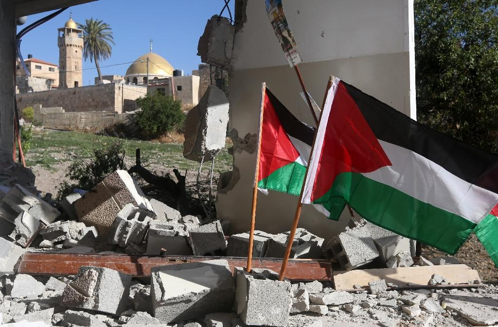 Palestinian flags are placed in the rubble of a demolished house belonging to a Palestinian man who carried out a knife attack in Tel Aviv on March 8, 2016 (AFP Photo/Jaafar Ashtiyeh)