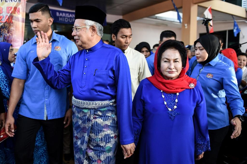 Former prime minister Najib Razak (C) and his wife Rosmah Mansor (R) are facing charges linked to a multi-billion dollar scandal at state fund 1MDB