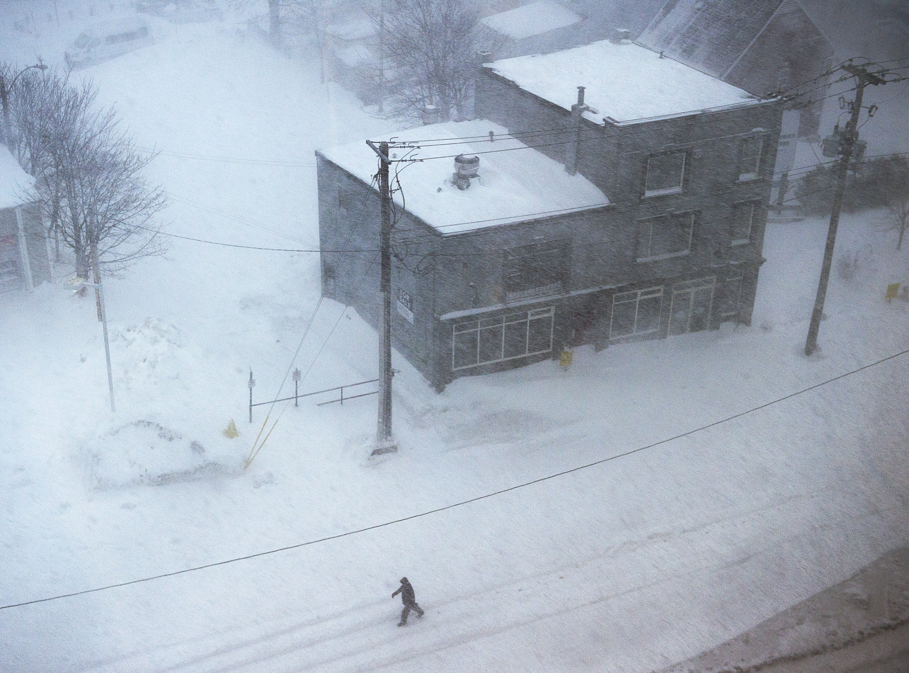 A man walks down the middle of New Gower St. as snow falls in St. John' Newfoundland on Friday, Jan. 17, 2020. The city has declared a state of emergency, ordering businesses closed and vehicles off the roads as blizzard conditions descend on the Newfoundland and Labrador capital. *Andrew Vaughan/The Canadian Press via AP)