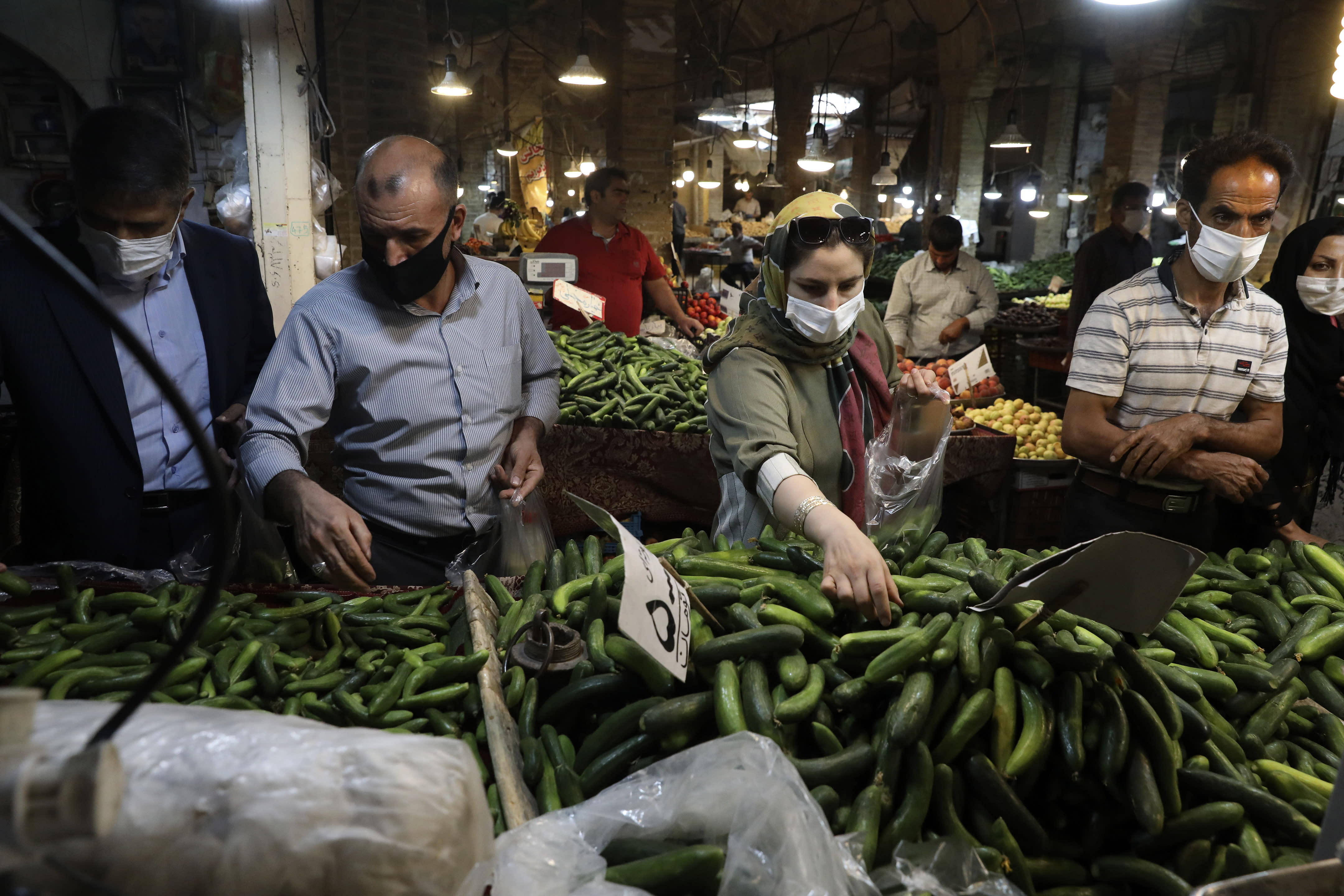 People wearing face masks to help prevent the spread of the coronavirus shop at the old grand bazaar of the city of Zanjan, some 330 kilometers (205 miles) west of the capital Tehran, Iran, Sunday, July 5, 2020. Iran on Sunday instituted mandatory mask-wearing as fears mount over newly spiking reported deaths from the coronavirus, even as its public increasingly shrugs off the danger of the COVID-19 illness it causes. (AP Photo/Vahid Salemi)