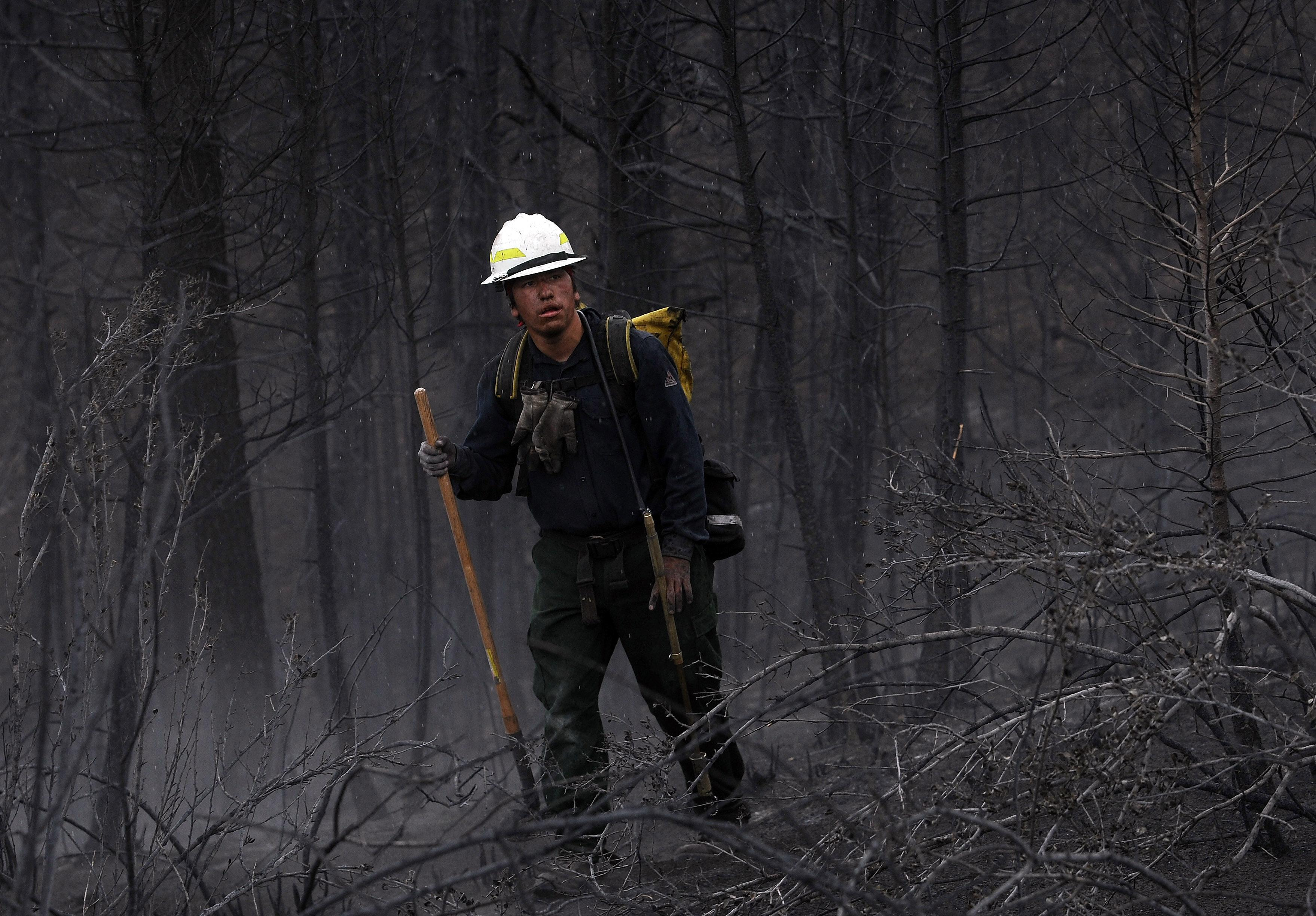 "A firefighter from the Bighorn 209, a hand crew from the Crow Agency in Montana, check for hot spots on the Waldo Canyon Fire west of Colorado Springs, Colo., Friday, June 29, 2012. After declaring a ""major disaster"" in the state early Friday and promising federal aid, President Barack Obama got a firsthand view of the wildfires and their toll on residential communities. More than 30,000 people have been evacuated in what is now the most destructive wildfire in state history. (AP Photo/The Gazette, Christian Murdock)"