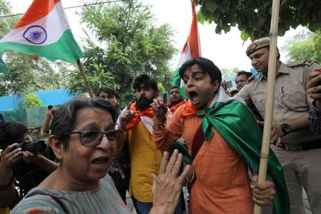 A woman, who was protesting against the scrapping of special constitutional status for Kashmir, argues with people who were celebrating the removal of the special status, during a gathering in New Delhi