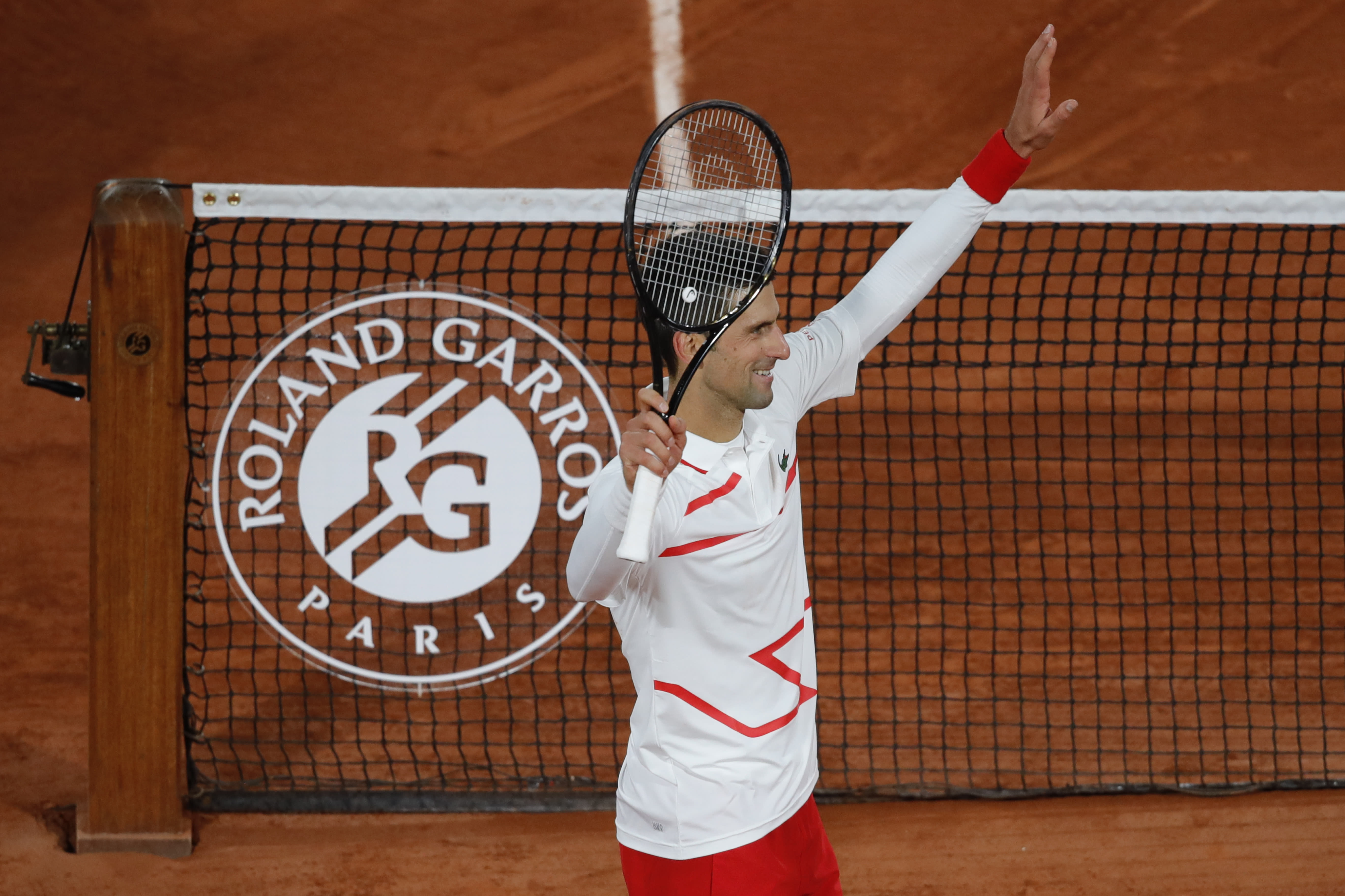 Serbia's Novak Djokovic celebrate winning his third round match of the French Open tennis tournament against Colombia's Daniel Elahi Galan in three sets 6-0, 6-3, 6-3, at the Roland Garros stadium in Paris, France, Saturday, Oct. 3, 2020. (AP Photo/Christophe Ena)